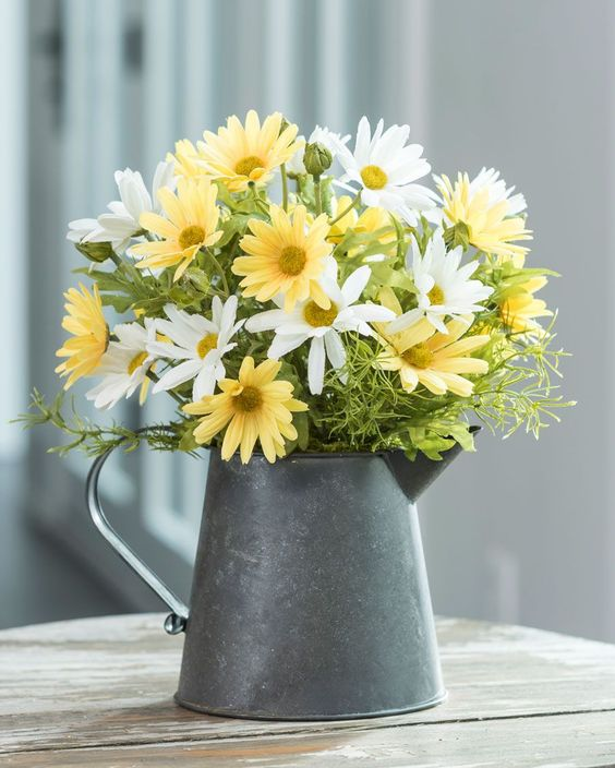 a metal teapot with bright summer blooms for a rustic summer feel in your space