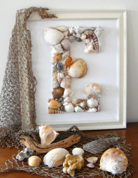 a monogram seashell artwork and some corals and seashells on fishing net for coastal and beachy decor