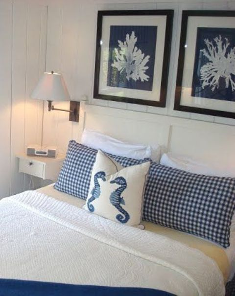 a nautical bedroom with coral artworks, nautical bedding and simple white furniture is a very fresh and cool idea to rock