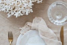 a neutral tablescape with a coral centerpiece feels coastal and beachy at once and looks very pretty
