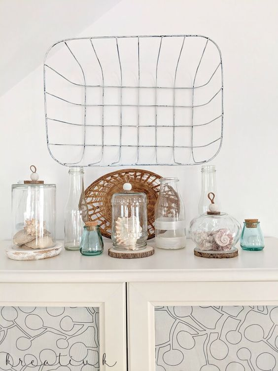 a pretty beach display with seashells and corals in jars and cloches plus blue bottles and a wicker basket