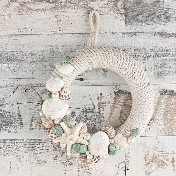 a pretty rope wreath with starfish, seashells and various pearls looks very coastal or beachy