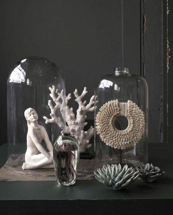 a refined decor composition of corals, a statuette, some creative decorations in cloches is a lovely idea for a sophisticated space