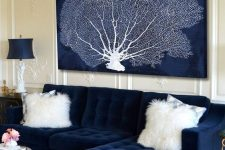 a refined nautical living room with a navy sofa and a dried coral artwork, refined lamps and a rug is amazing