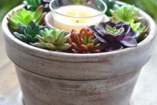 a simple decoration or centerpiece of a whitewashed planter with succulents and a candle in the center