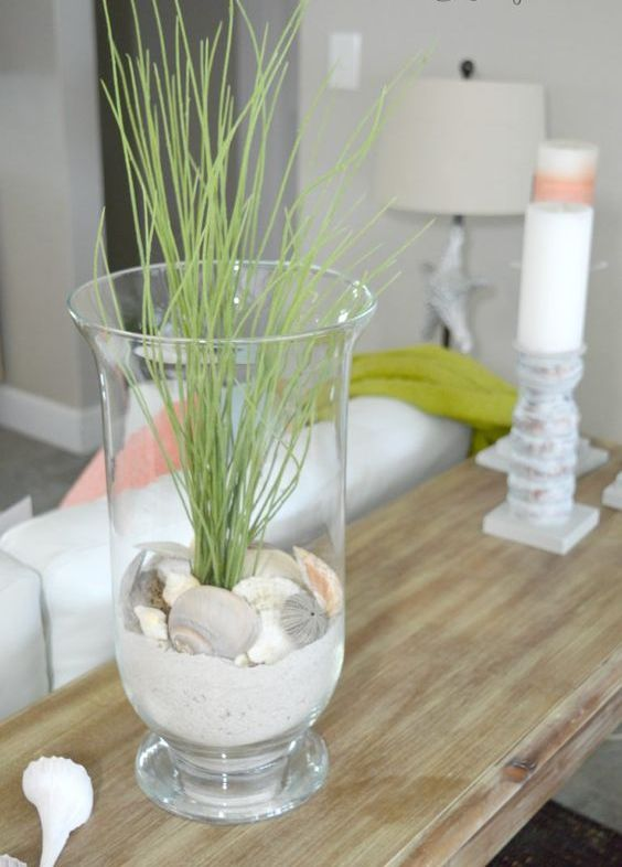 a tall glass with beach sand, seashells and some grass for decorating your console table