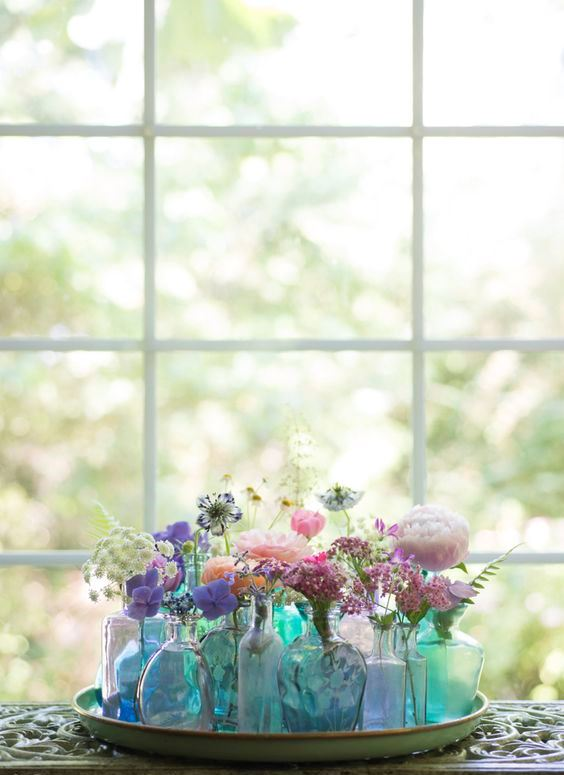 a tray with an arrangement of blue and green bottles and vases with colorful blooms