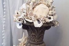 a vintage urn with seashells, corals and other stuff is a lovely idea for a seaside space, an outdoor or an indoor one