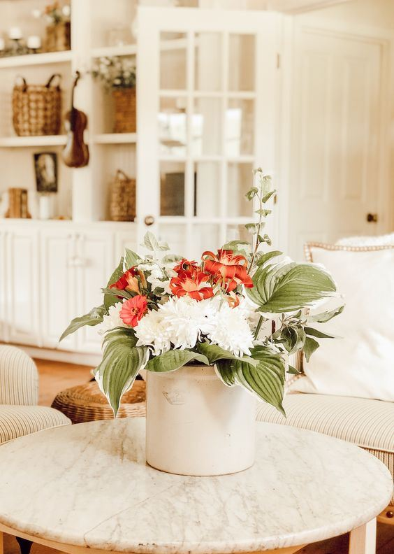 a white metal bucket with red and white blooms and oversized leaves for a simple and cool summer bouquet