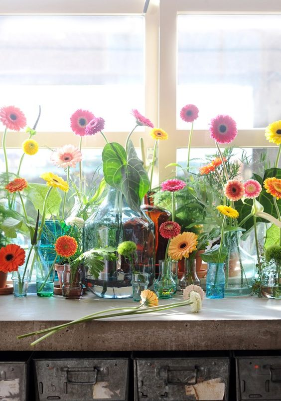 a whole arrangement of colorful bottles, jars and vases with lots of bright gerberas is a lovely summer idea