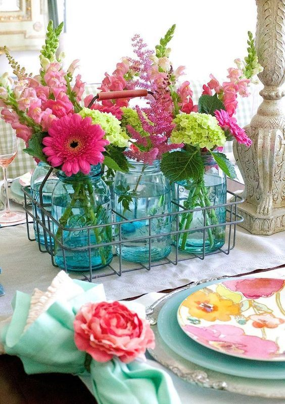 a wire basket with blue jars and pink and green blooms for a slight rustic touch and a strong summer feel