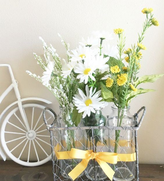 a wire basket with bottles and white and yellow blooms is a chic and simple rustic decoration