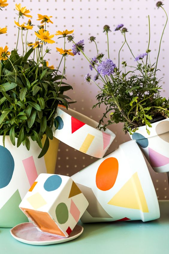 an arrangement of colorful print pots attached to each other and with bright summer blooms is lovely