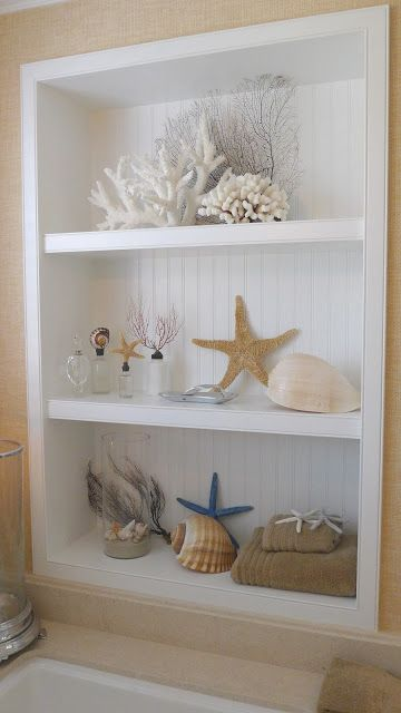 an open storage unit with corals, starfish, seashells and other sea stuff is a lovely decor idea for a living room or some other space