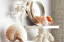 bathroom shelves with faux corals attached to them and with seashells and a mirror on them for giving a seaside feel to the space