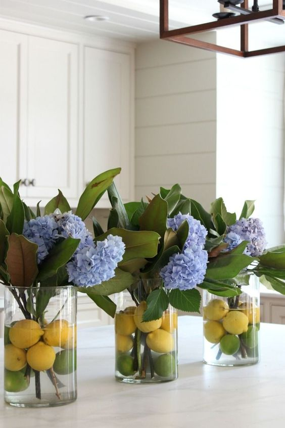 clear vases with citrus and blue hydrangeas and magnolia leaves for chic traditional southern decor