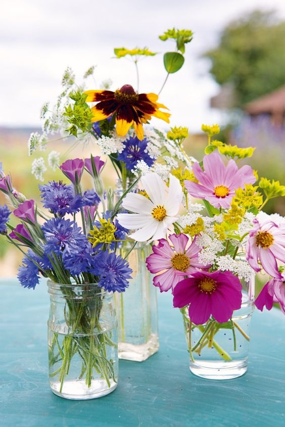 jars and glasses with bright blooms and white ones will compose a cool summer centerpiece