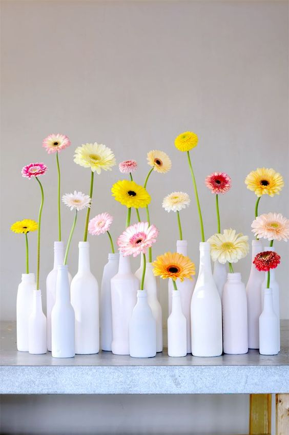 white bottles with colorful gerberas for a modern and bold summer decoration that is easy to compose