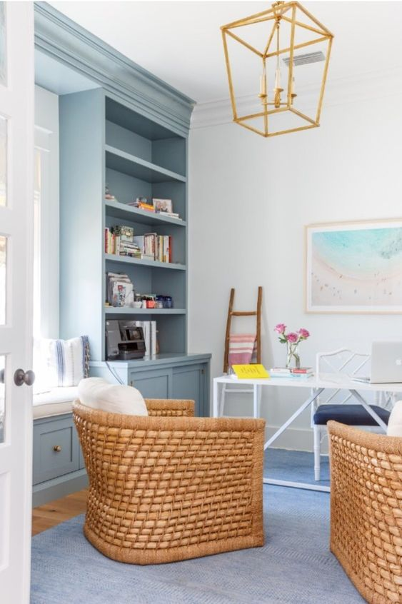 a beach home office with light blue storage units and a built-in daybed, an airy desk and rattan chairs and a gilded chandelier
