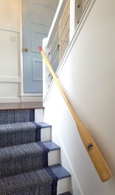 a beach staircase in blue and white covered with a navy carpet and with rope and oar railings is amazing