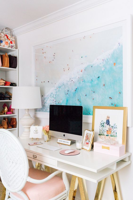 a beachy home office nook with a large beach photo, a white and gold desk, a pink chair and a chic table lamp is amazing
