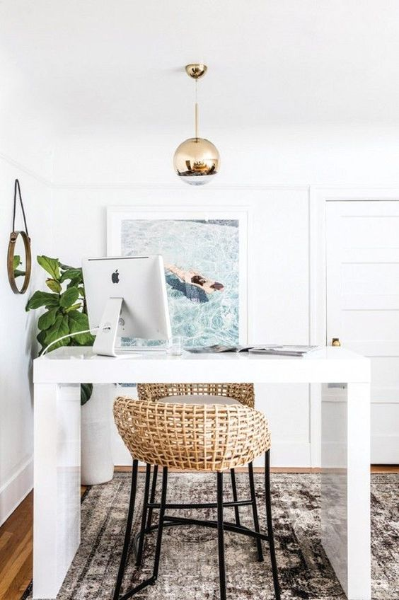 a beachy home office with a tall white desk, a couple of rattan stools, a beach photo and a statement potted plant