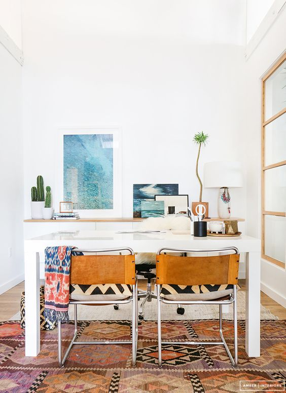 a boho coastal home office with a white desk, leather chairs, a white storage unit, sea-inspired artworks and potted plants