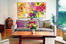 a bold floral artwork, bold blooms in a vase and colorful pillows to make your living room extra bold