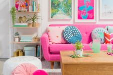 a bold living room with colorful artworks, a pink sofa and pink and blush pillows plus printed ones