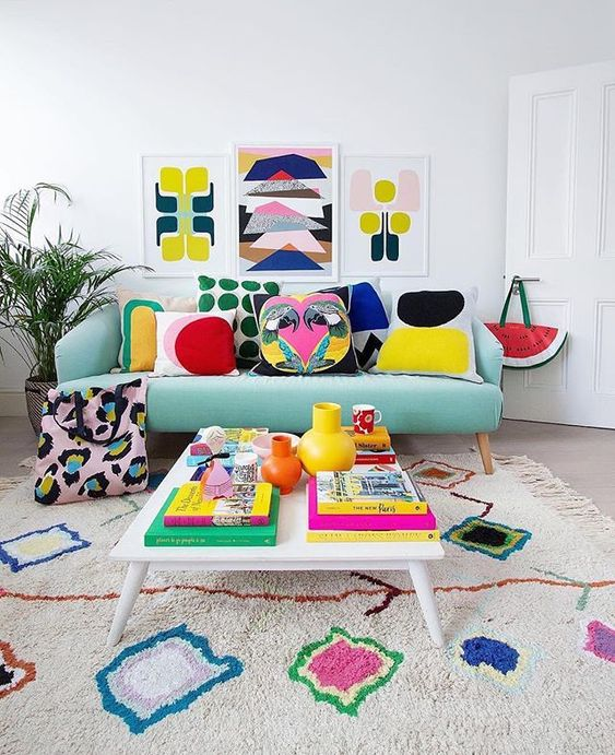a bold summer living room with a colorful gallery wall, bright printed pillows and a rug plus bright books and vases