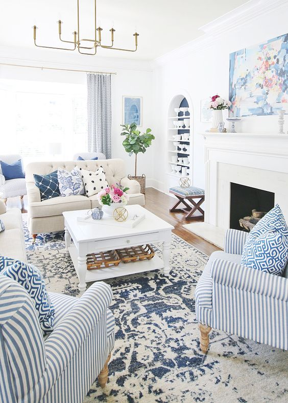 a bold summer living room with a printed rug, bold printed pillows and a striped chair plus greenery and blooms
