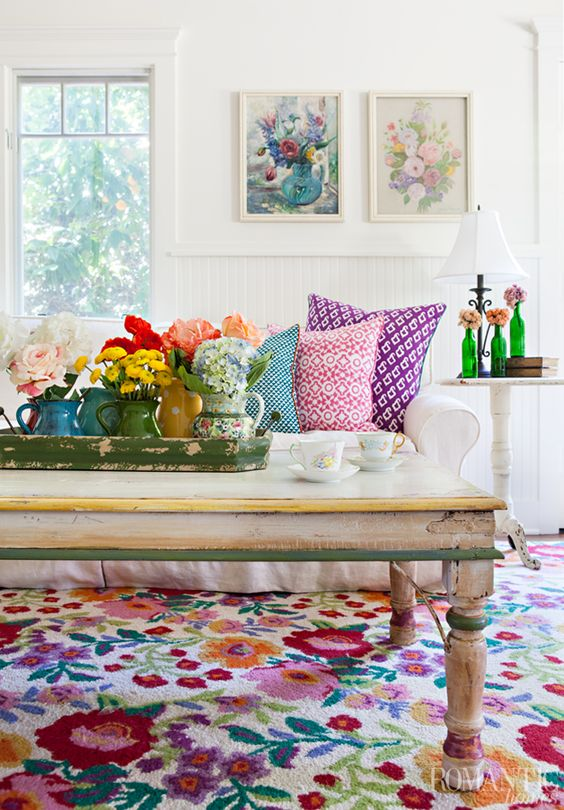 a bold summer living room with floral artworks, blooms in vases, printed pillows and a colorful floral rug for a cheerful feel