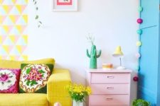 a bright geometric hanging, a yellow sofa, a pink dresser, colorful garlands and blooms and greenery in pots