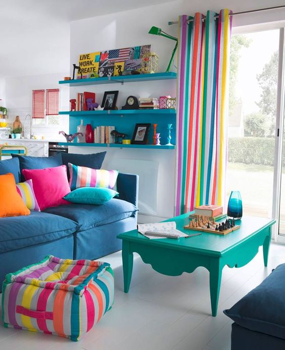 a bright living room with striped curtains, a matching ottoman, colorful pillows and some bold furniture for fun