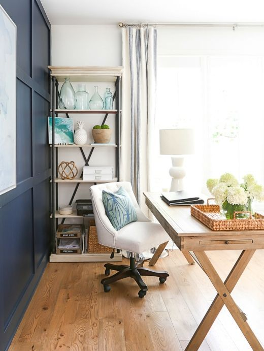 a coastal beach home office with a navy accent wall, a wooden trestle desk, an upholstered chair and a storage unit