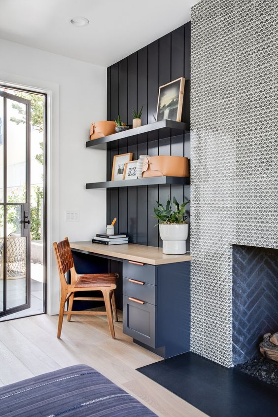 a coastal home office with a navy wall, a navy desk with a stone desktop, a wood and leather chair and a fireplace is welcoming