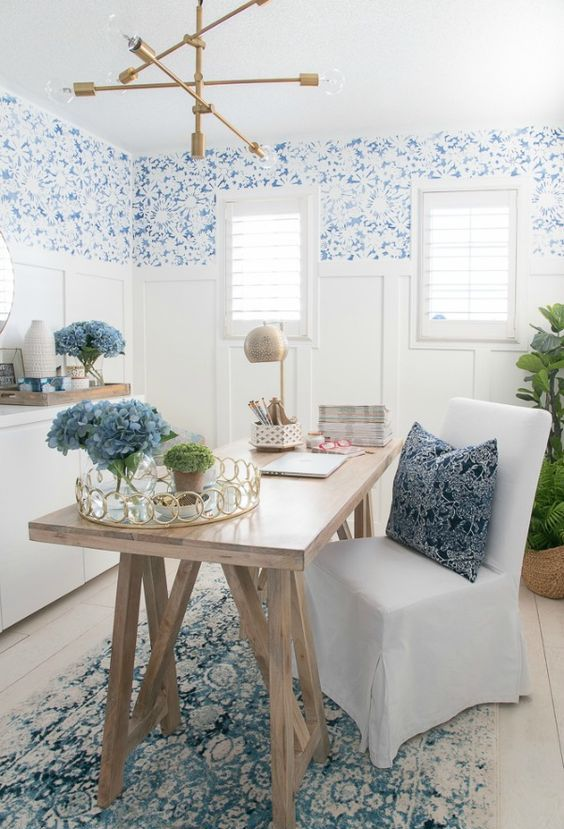 a coastal home office with blue printed wallpaper, white paneling, a trestle desk, an upholstered chair and a gilded chandelier