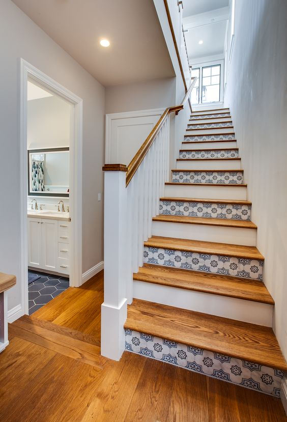 a coastal staircase with risers painted white and clad with blue patterned tiles is a beautiful idea for a seaside home
