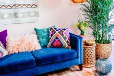a colorful boho living room with a boho hanging, faceted lamps, a blue sofa, colorful pillows and a rug