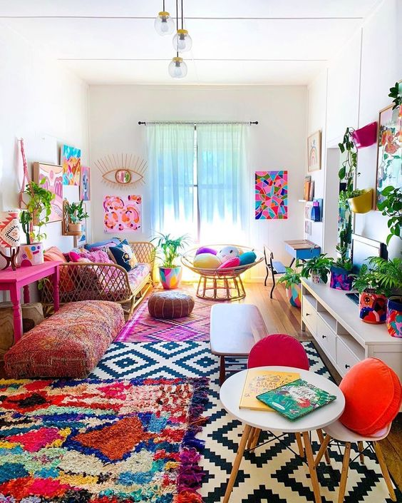 a colorful boho living room with a bright gallery wlal, colorful rugs and pillows, potted greenery and florals is summer-like