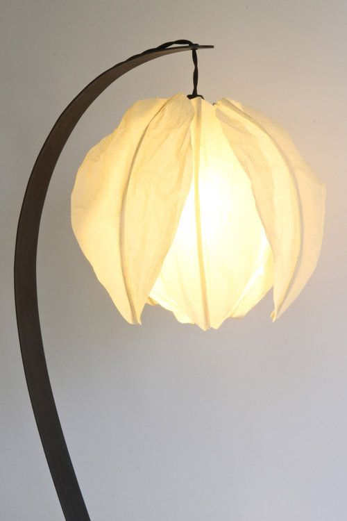 a curved table lamp with a flower-shaped lampshade looks very pretty and very chic