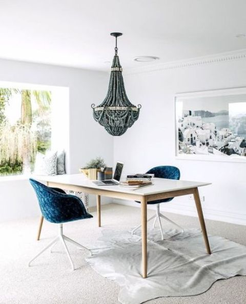 a fabulous coastal home office with a glazed wall, a desk, navy chairs, a wooden bead chandelier and a sea-inspired artwork