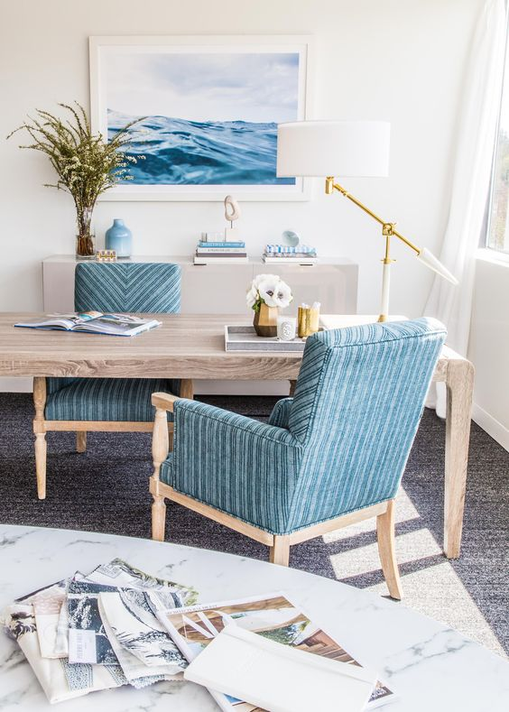 a gorgeous seaside home office with a wooden desk, blue chairs, a sea-inspired artwork, an elegant and catchy table lamp