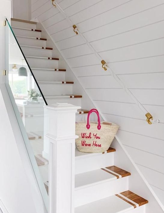 a modern beach staircase with stained and white painted steps, acrylic and gold railing and clear railing is amazing