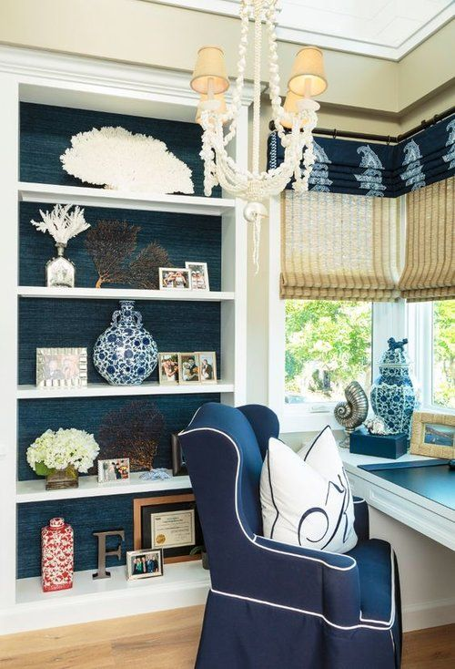 a nautical home office with navy walls, a white storage unit, a white desk, a navy chair, a chic chandelier and shades and curtains
