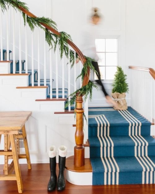 a nautical staircase with a seaside feel achieved with blue and white striped carpet covering all the steps