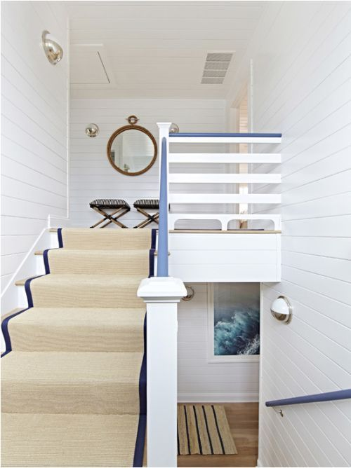 a nautical staircase with tan and navy striped carpet and navy railing is a chic and elegant idea for a nautical home
