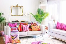 a neutral living room infused with bold printed pillows and tropical plants in pots for a summer feel