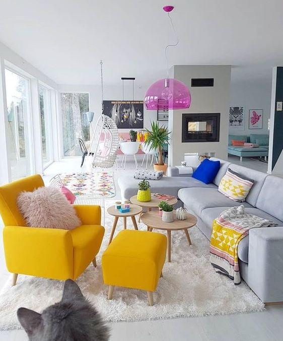 a neutral living room with a bright yellow chair, boho textiles, a pink pendant lamp and potted plants