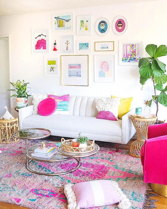 a neutral living room with colorful pillows, a bright printed rug, a colorful gallery wlal and potted greenery here